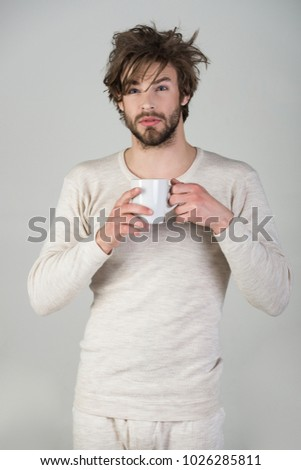 Cold and flu, single. Man with disheveled hair drink mulled wine. Sleepy guy with tea cup on grey background. Morning with coffee or milk. Insomnia, refreshment and energy.