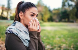Cold and flu. Woman blowing her nose with a tissue