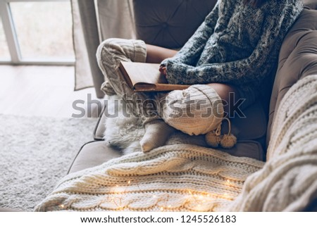 Cold autumn or winter weekend while reading book. Lazy day in warm knit clothing on the couch. Cosy scene, hygge concept. #1245526183
