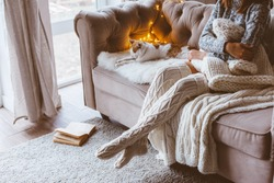 Cold autumn or winter weekend while relaxing with cat on a couch. Lazy day in knitted socks at home. Cosy scene, hygge concept.