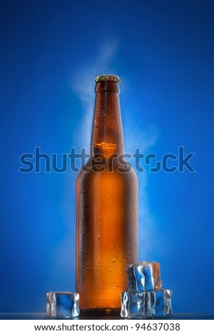 Cold beer bottle with drops, frost and vapour on blue
