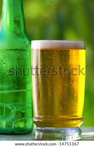 Cold beer in glass with green bottle.