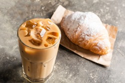Cold black coffee with ice cubes in tall glass and fresh croissant. Refreshing coffee drink on a table gray background.