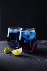 Cold blue tea with pieces of ice and lime in a transparent glass on a black background in a dark key, the concept of a cool drink, vertical background, selective focus