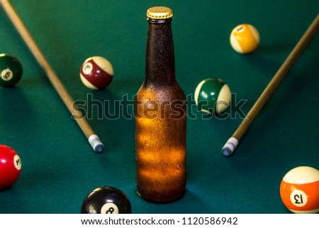 Cold bottle of beer on a green billiard table, billiard balls