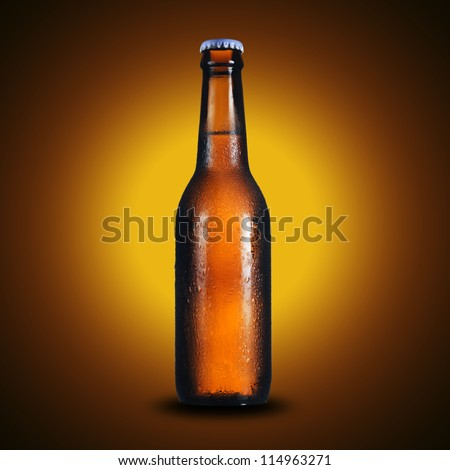 Cold bottle of light beer on yellow background