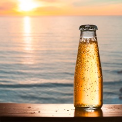 Cold bottled drink in focus with gas and amazing blurred view of sea