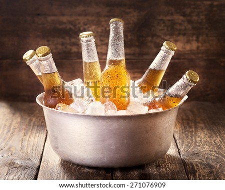 cold bottles of beer in bucket with ice on wooden table #271076909