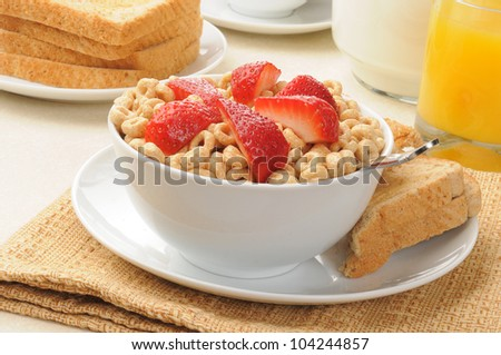 Cold breakfast cereal with fresh strawberries and buttered toast