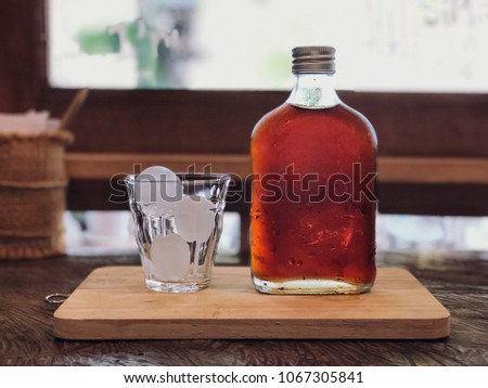 Cold brew coffee bottom and glass on the wooden tray with cafe light. Relaxing with ice coffee. #1067305841