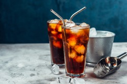 Cold brew coffee in a two glass with metal straw on a dark background.Iced coffee with ice cube.