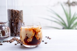cold brew coffee with milk on white wooden table