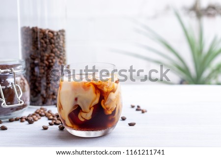 cold brew coffee with milk on white wooden table  #1161211741