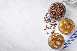 Cold brewed iced coffee in glass and coffee beans in glass jar on white background. Top view, copy space.