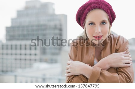 Cold casual blonde posing outdoors on urban background