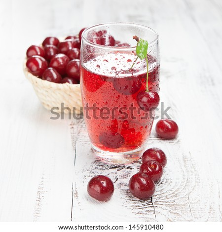 Cold cherries drink with fresh cherry on white wooden table