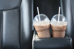 Cold chocolate in a clear plastic cup, two glasses placed in the glass holder in the car