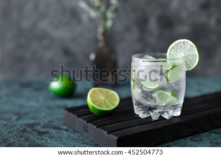 Cold cocktail with lime, tonic, vodka and ice on dark background Zdjęcia stock ©