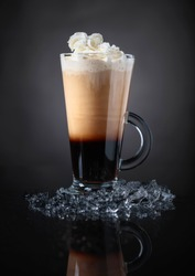 Cold coffee drink or cocktail with cream on a black background.