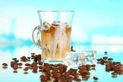 Cold coffee with ice in glass on blue background