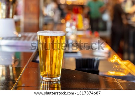 Cold craft beer in a glass with water drops.  Pint of beer close up isolated on a bar background