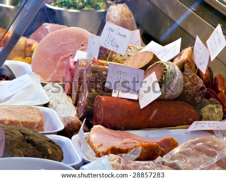 cold cuts meats and sausages on display for sale in a deli