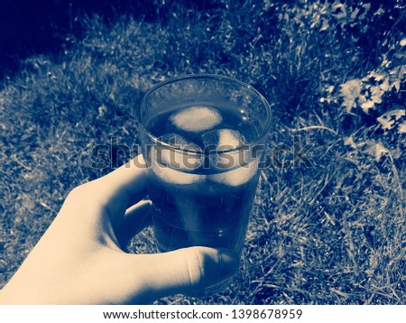 Cold dark blue soda drink with ice and bubbles being held by a hand. Grass can be seen in the distance. black, white and blue picture. Sweet beverage.