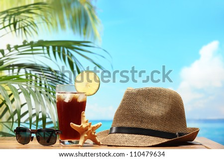 Cold drink and straw hat on beach