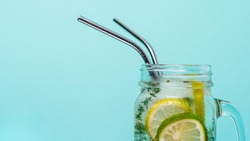 Cold drink in mason jar with metal straw on blue background. Lemonade or detox water with lime and thyme in glass jar with copy space for text or design. Recyclable straws, zero waste concept. Banner.
