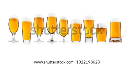 Cold elegant glasses of lager beer with foam and dew isolated on white background