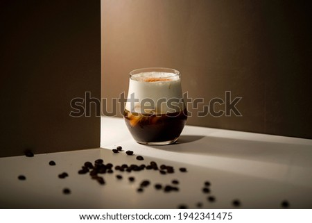 cold espresso coffee with cold milk foam with coffee with brown background  and sprinkled coffee beans on white table