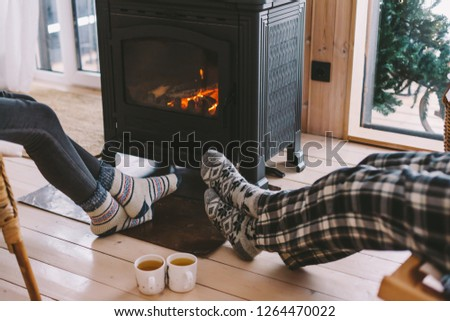 Cold fall or winter day. People drinking tea and resting by the stove. Closeup photo of human feet in warm woolen socks over fire place. Hygge concept of cozy winter weekend in cabin. Stock fotó ©