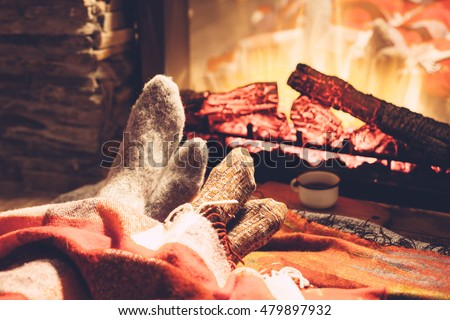 Stock Photo Cold fall or winter evening. People resting by the fire with blanket and tea. Closeup photo of feet in woolen socks. Cozy scene.