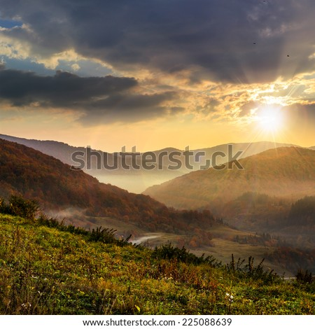 cold fog over red autumn trees in  mountains at sunset