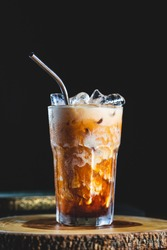 Cold fresh thai ice tea coffee served with coconut milk and metal straw with ice cubes on wood table and black background
