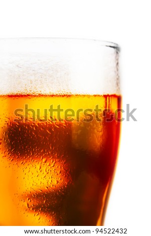 cold glass of beer with foam on a white background