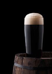 Cold glass of dark stout beer on wooden barrel on black background