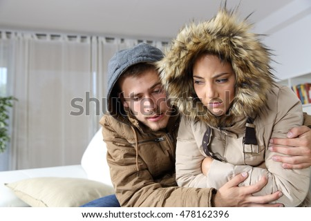 Cold home with an angry couple warmly clothed hugging sitting on a sofa in the living room #478162396