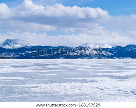 Cold icy winter landscape of frozen Lake Laberge, Yukon Territory, Canada