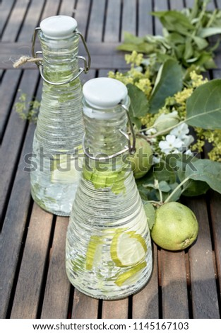 Cold infused water in glass bottles with apple and herbs on a rustic slatted wood garden table