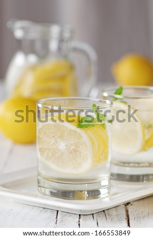 Cold lemon water with ice and mint, selective focus