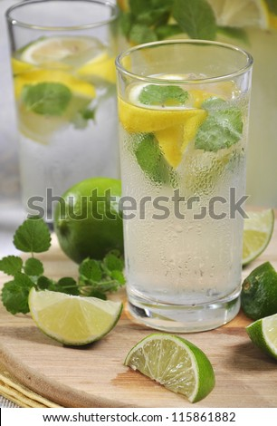 Cold lemonade in glass with ice, lime and lemon on cutting board