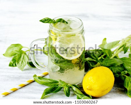 Cold lemonade with basil and lemon on a light background. Soft focus. Place for text. Copy Space