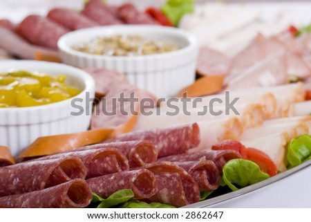 Cold meat catering platter with sliced chicken breast, mortadella, salami, roast beef, ham, turkey, kabana sausage and seeded wholegrain mustard and sweet mustard pickle.