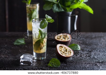 Cold mojito with passion fruit, mint and ice on the black background #406737880