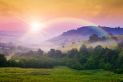 cold morning fog with red hot sunrise and rainbow in the mountains