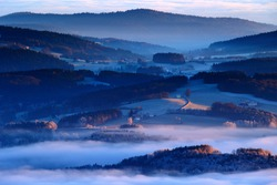 Cold morning in Sumava National park, hills and villages in the fog and rime, misty view on czech landscape, blue winter scene, Tristolicnik, Czech Republic.