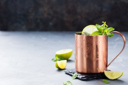 Cold Moscow Mules cocktail with ginger beer, vodka, lime. Grey stone background. Copy space.