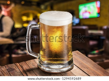 Cold mug of light beer on the bar counter. Pub interior at the background.