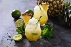 Cold pineapple cocktail with crushed ice, lime and mint, refreshing lemonade drink